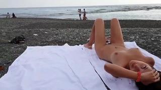 십대는 완전히 알몸으로 야외 해안에서 일광욕을합니다.
