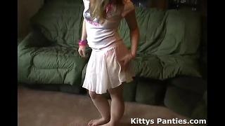 Kleine Teenager-Katze, die ihr Höschen in einem kleinen Minirock blinkt